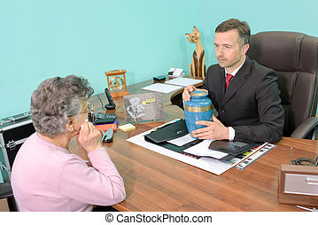 Funeral director in meeting with woman, holding an urn