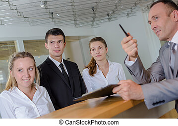 Man at reception desk with young staff pointing left