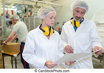 Two factory workers looking at paperwork