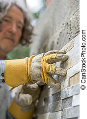 Low angle view of male worker pressing an ornamental tile into a glue on a wall