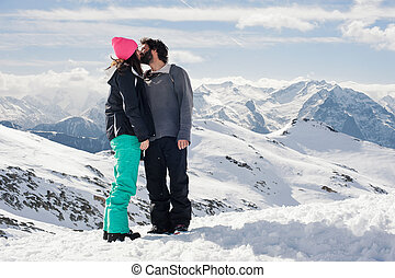 Couple kissing in the snow - Young couple in love kissing on...
