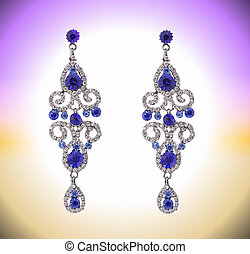 long earring with blue stones and zircons on a abstract...