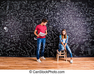 Beautiful young students in front of big blackboard