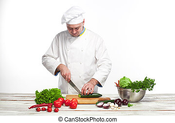 Chef cutting a green cucumber in his kitchen - The chef...