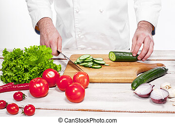 Chef cutting a green cucumber in his kitchen - The hands of...