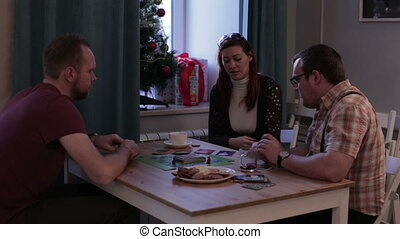 Woman and two men playing a board game with cards -...