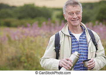 Senior Man Pouring Drink From Flask On Walk