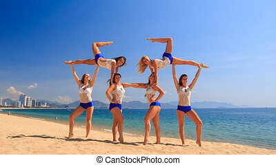 cheerleaders in white blue show Swedish falls on beach -...