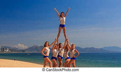 cheerleaders in white blue show half stunt pyramid on beach...