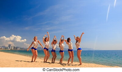 cheerleaders in uniform group do Toe Touch Basket Toss on beach