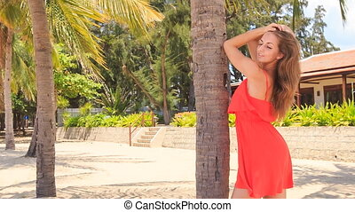 blond girl in red leans on palm trunk speaks against villa