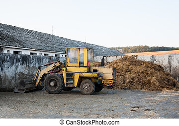 Old bulldozer near heap of manure - An old loader and pile...
