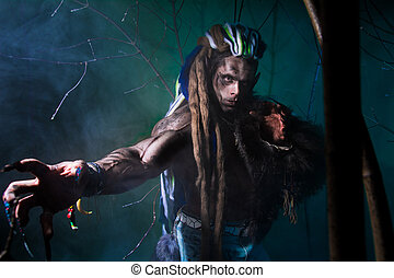 Muscular werewolf with dreadlocks with long nails among the...