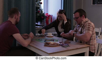 Men and woman playing a board game with cards - Caucasian...