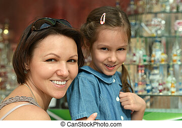Mother with daughter near souvenir shop - Happy mother with...