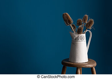 Wide Angle View of Old Vase with Thistles on Stool