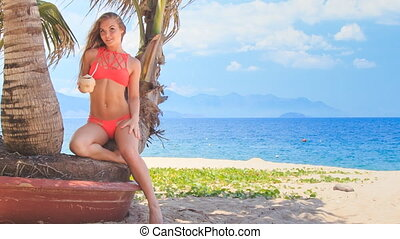 blond girl in bikini sits on palm holds coconut bent knee -...