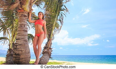 camera approaches to blond girl in bikini standing on palm...