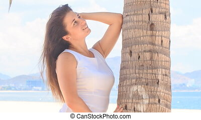girl with big bust in white leans on palm trunk with elbow -...