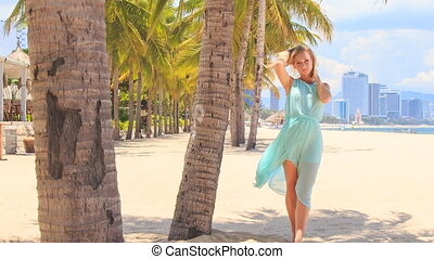 blonde girl in azure lifts hands walks among palms on beach...