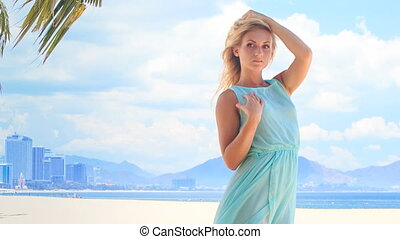 blonde girl in azure touches hair bust under wind on beach -...