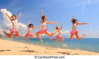 cheerleaders in uniform dance in jump stunt on beach against sea