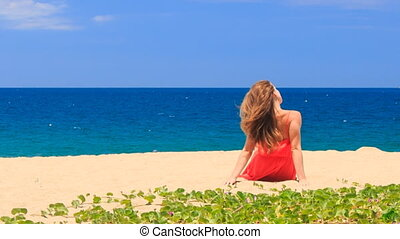 blond girl in red sits barefoot on sand turns to camera