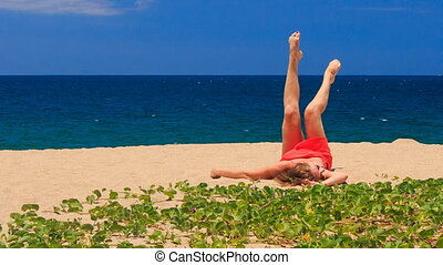 blond girl in red lies on sand does scissors by legs at...