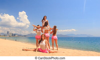 cheerleaders show split swing stunt dance on beach against...