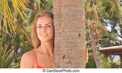 closeup blond girl in red touches palm smooths hair -...
