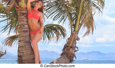 blond girl in bikini leans on palm smoothes hair against sky