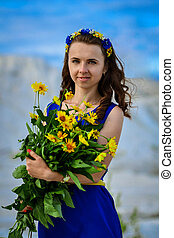 Beautiful cute girl in long blue dress with bouquet of...