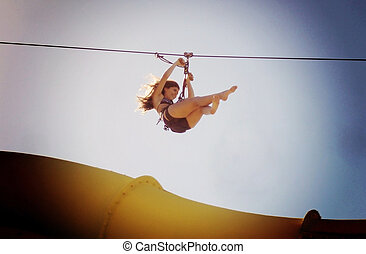 Zipline in waterpark - A teenager is fling down in a zipline...