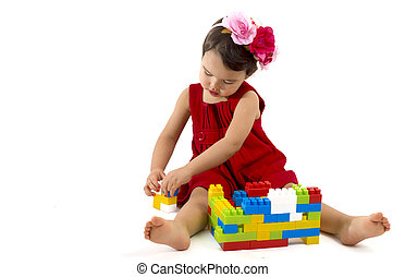 funny child girl playing with construction set over white background