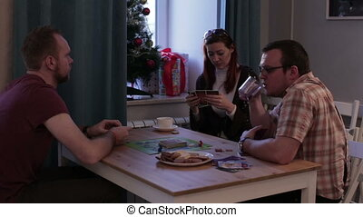 Group of people playing a board game with cards - Caucasian...