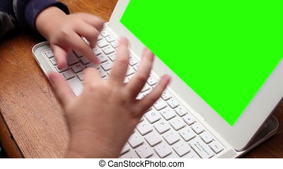 Hands of young child typing on keyboard