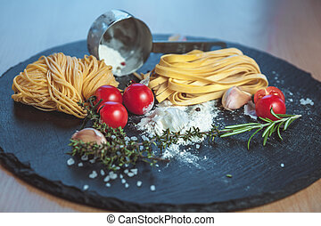 Beautiful fresh spaghetti on the blackboard with spices and...