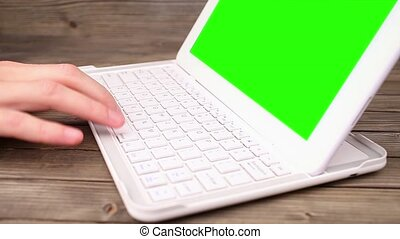 A man types on a laptop on his desk Green screen for your...