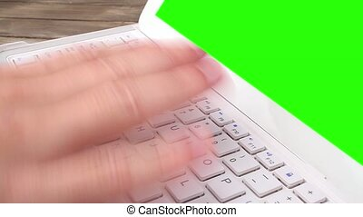 A man types on a laptop on his desk. Green screen for your...