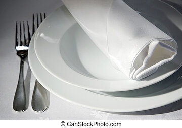 Napkin on tables - Dinner table detail with dishes, forks...
