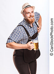 Happy smiling man with leather trousers lederhose holds...