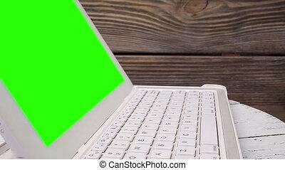 Laptop rotating, wood background