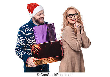 Beautiful couple with Christmas gifts isolated on a white background in a Santa hat