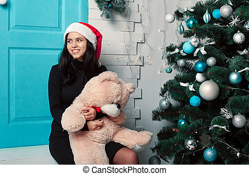 Beautiful girl in a Christmas room with a toy bear