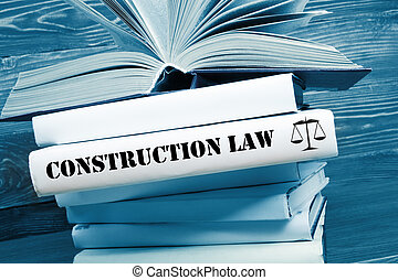 Book with Construction Law word on table in a courtroom or enforcement office. Toned image