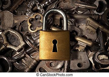 Padlock over keys - Keyhole on a golden padlock over many...