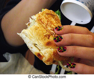 Sub Sandwich for Lunch - A closeup view on a woman eating a...
