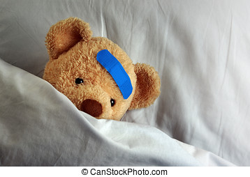 Teddy in Bed - Photo of a sick teddy bear with a blue...