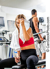 Tired slim woman with towel on bench in gym.