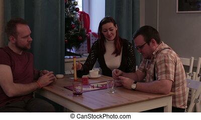 Couple with friend to play a board game in a cafe -...